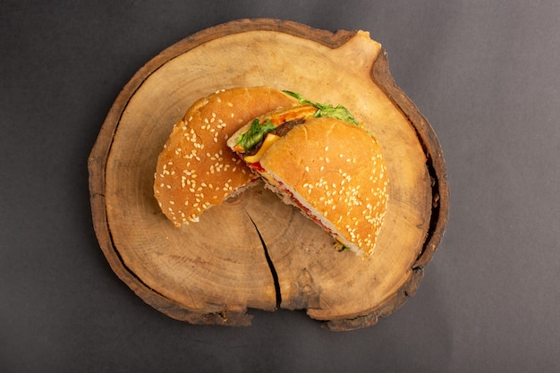 Bovenaanzicht van gesneden broodje kip half gesneden op het donkere oppervlak
