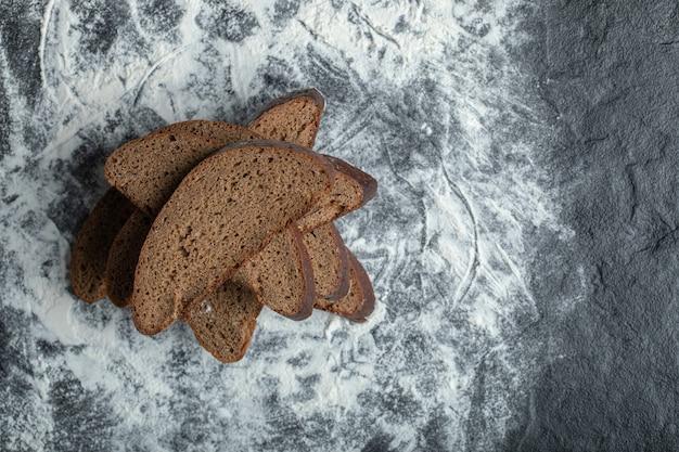 Bovenaanzicht van gesneden bruin brood op bloem achtergrond.