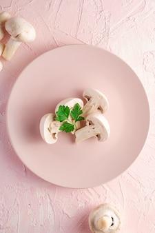 Bovenaanzicht van gesneden champignons met peterselie bladeren op roze plaat