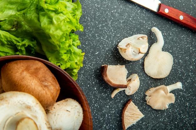 Bovenaanzicht van gesneden champignons met sla en keukenmes op zwarte bord