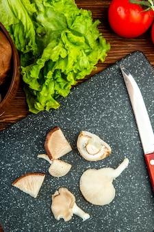 Bovenaanzicht van gesneden champignons met sla tomaat en keukenmes op zwarte bord op hout