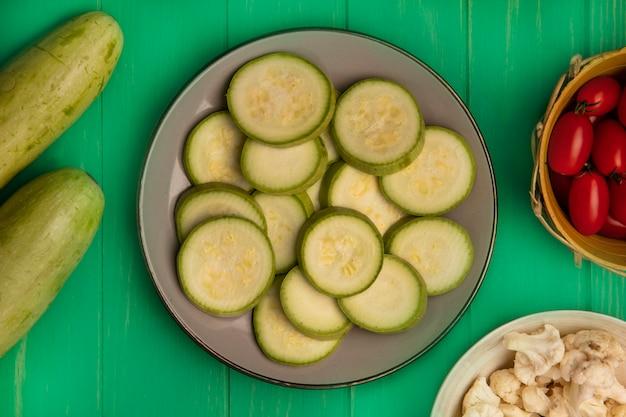 Bovenaanzicht van gesneden courgette plakjes op een bord met pruimtomaten op een emmer met bloemkoolroosjes op een kom met courgettes geïsoleerd op een groene houten muur