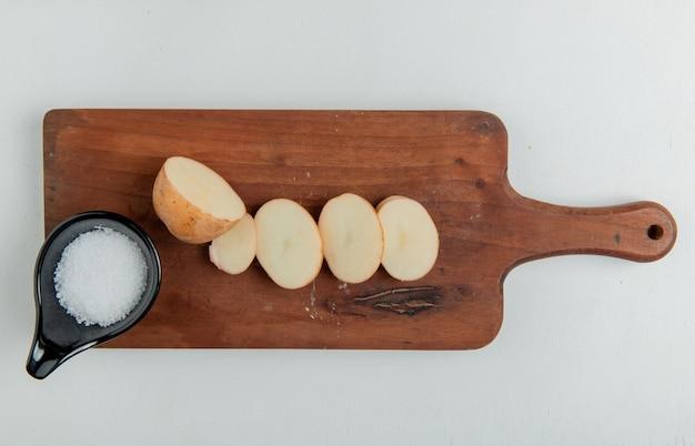 Bovenaanzicht van gesneden en gesneden aardappel en zout op snijplank op wit