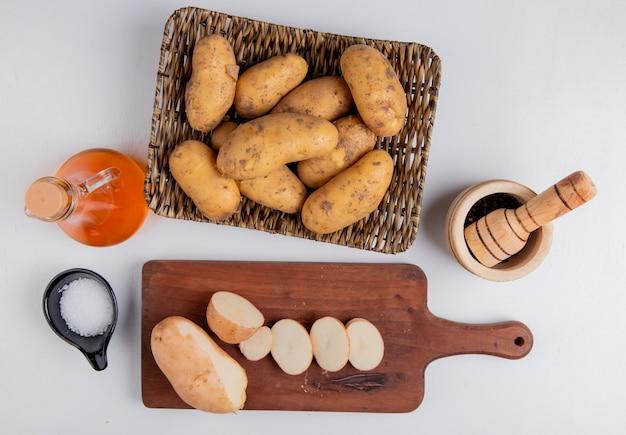 Bovenaanzicht van gesneden en gesneden aardappel op snijplank met andere in mand plaat met zout zwarte peper gesmolten boter op witte ondergrond