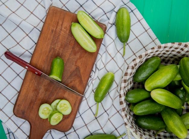 Bovenaanzicht van gesneden en gesneden komkommer met mes op snijplank met hele degenen in mand op geruite doek en groen oppervlak