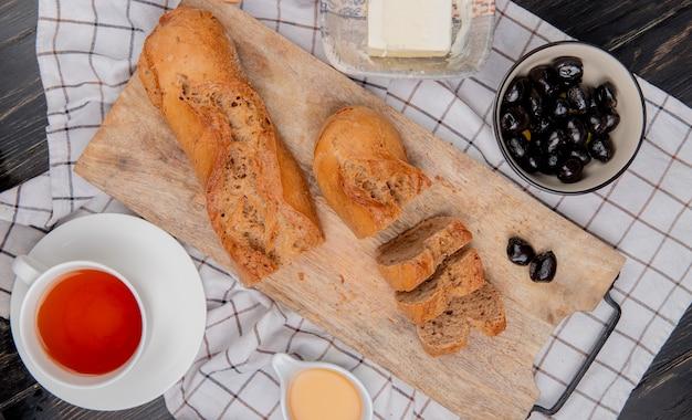 Bovenaanzicht van gesneden en gesneden zwarte stokbrood met kopje thee boter olijfolie op geruite doek en houten tafel