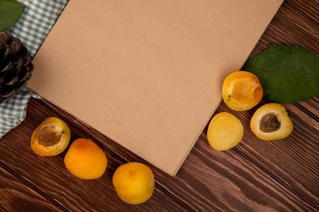 Bovenaanzicht van gesneden en hele abrikozen met verlof en dennenappel en notitieblok op houten achtergrond