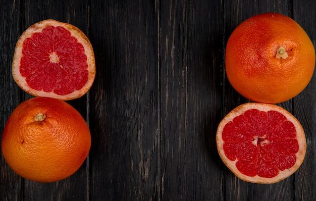 Bovenaanzicht van gesneden en hele grapefruits aan de linker- en rechterkant en een zwarte achtergrond met kopie ruimte