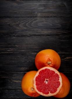 Bovenaanzicht van gesneden en hele grapefruits op zwarte achtergrond met kopie ruimte