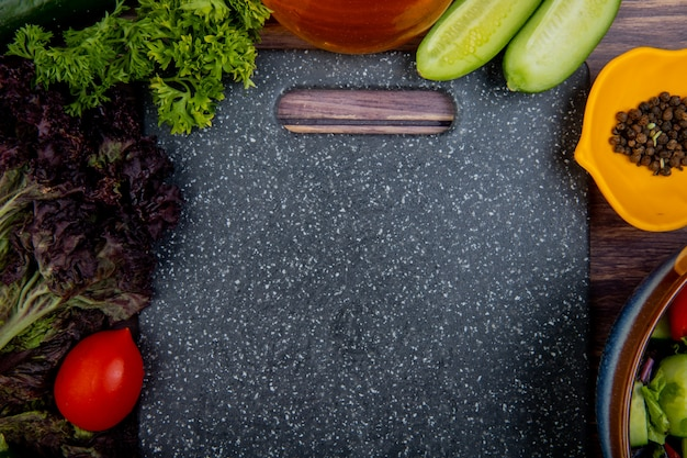 Bovenaanzicht van gesneden en hele groenten als tomaat basilicum munt komkommer koriander met zwarte peper en snijplank op houten oppervlak