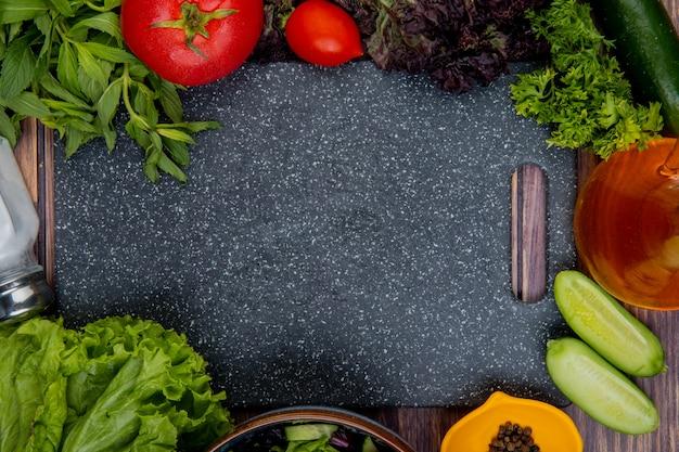 Bovenaanzicht van gesneden en hele groenten als tomaat, basilicum, munt, komkommer, sla, koriander met zout, zwarte peper en snijplank op houten oppervlak