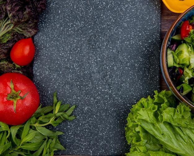 Bovenaanzicht van gesneden en hele groenten als tomaten, basilicum, munt, komkommersla met snijplank als oppervlak