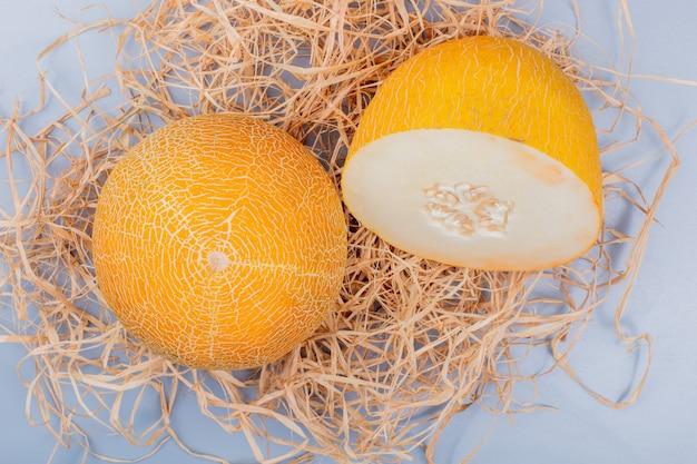 Bovenaanzicht van gesneden en hele meloenen op stro en blauwachtig grijze achtergrond