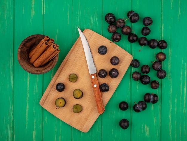 Bovenaanzicht van gesneden en hele sleedoornbessen met mes op snijplank en kaneel in kom op groene achtergrond