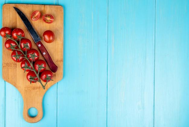 Bovenaanzicht van gesneden en hele tomaten met mes op snijplank op blauw met kopie ruimte