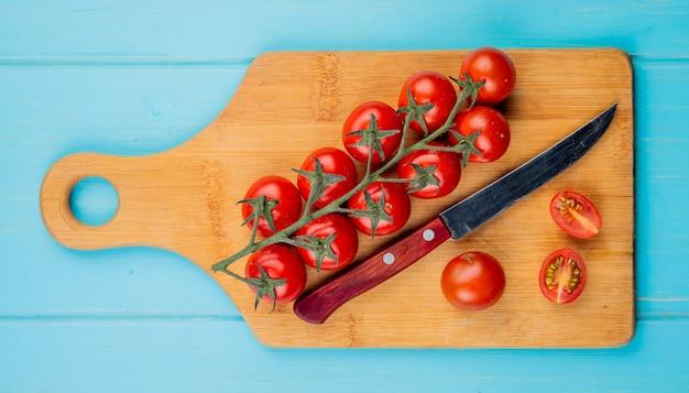 Bovenaanzicht van gesneden en hele tomaten met mes op snijplank op blauwe ondergrond