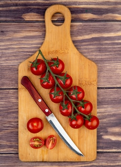 Bovenaanzicht van gesneden en hele tomaten met mes op snijplank op hout