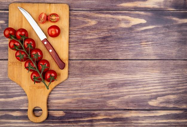 Bovenaanzicht van gesneden en hele tomaten met mes op snijplank op houten oppervlak met kopie ruimte