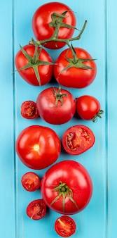 Bovenaanzicht van gesneden en hele tomaten op blauw