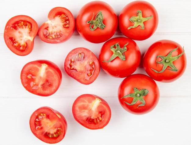 Bovenaanzicht van gesneden en hele tomaten op houten oppervlak
