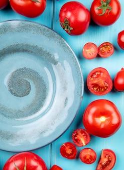 Bovenaanzicht van gesneden en hele tomaten rond plaat op blauw