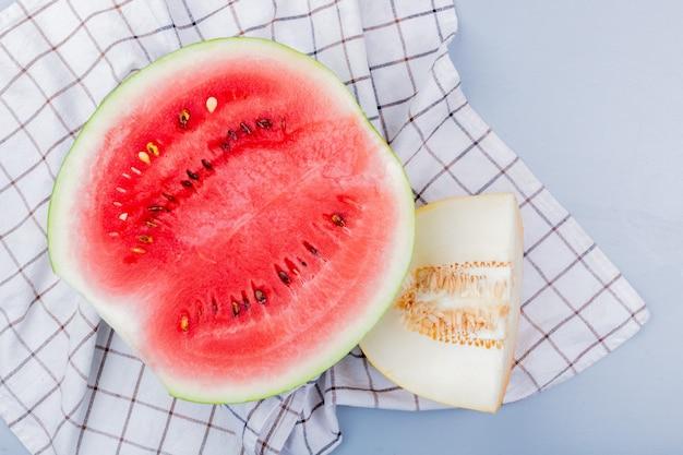 Bovenaanzicht van gesneden fruit als watermeloen en meloen op geruite doek en blauwachtig grijze achtergrond