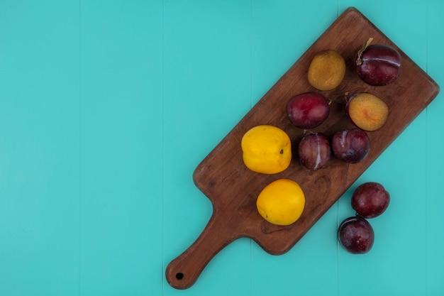 Bovenaanzicht van gesneden fruit en hele plukken en nectacots op snijplank en op blauwe achtergrond met kopie ruimte