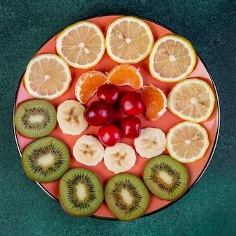 Bovenaanzicht van gesneden fruit kiwi citroen banaan mandarijn en rode kersen op plaat op donker