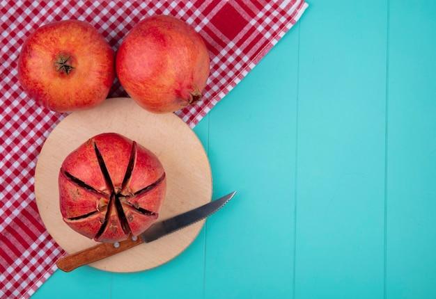 Bovenaanzicht van gesneden granaatappel met mes op snijplank en hele op blauw met kopie ruimte