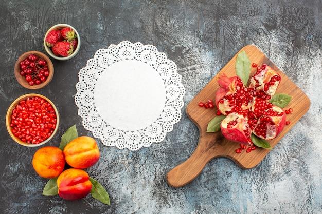 Bovenaanzicht van gesneden granaatappels met perziken op de donkere achtergrond