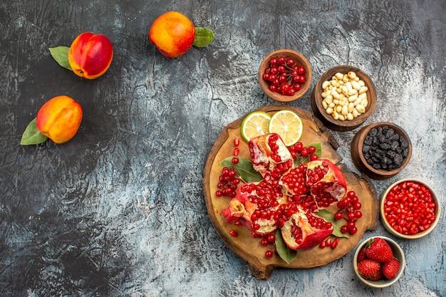 Bovenaanzicht van gesneden granaatappels met perziken op de licht-donkere achtergrond