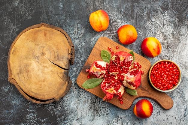 Bovenaanzicht van gesneden granaatappels met perziken op donker bureau