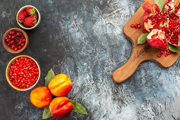 Bovenaanzicht van gesneden granaatappels met perziken op donkere vloer