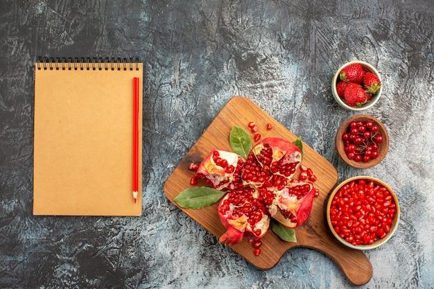 Bovenaanzicht van gesneden granaatappels met rode vruchten op donkere achtergrond