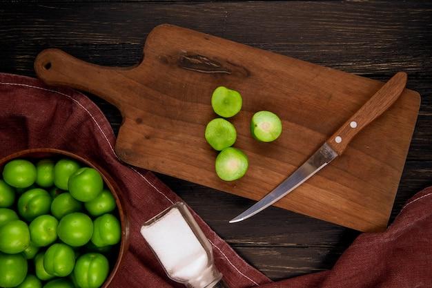 Bovenaanzicht van gesneden groene pruimen met een keukenmes op een houten snijplank met een kom gevuld met groene pruimen op donkere rustieke tafel