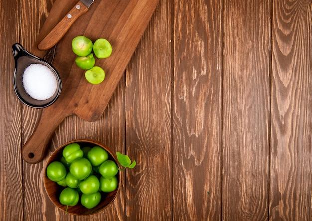 Bovenaanzicht van gesneden groene pruimen met zout en keukenmes op een houten snijplank en pruimen in een kom op rustieke houten tafel met kopie ruimte