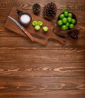 Bovenaanzicht van gesneden groene pruimen met zout en keukenmes op een houten snijplank, kegels en pruimen in een kom op rustieke houten tafel met kopie ruimte