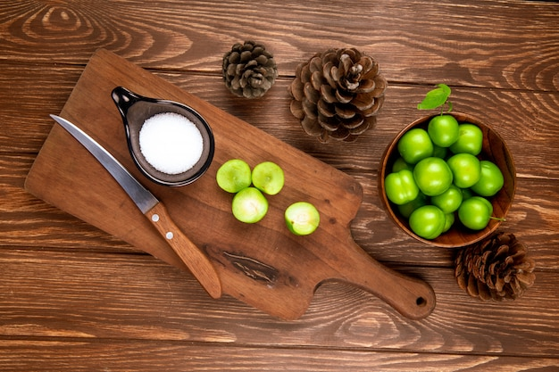 Bovenaanzicht van gesneden groene pruimen met zout en keukenmes op een houten snijplank, kegels en pruimen in een kom op rustieke houten tafel