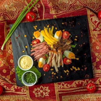 Bovenaanzicht van gesneden ham geserveerd met eieren, tomaten en sauzen op een zwarte bord