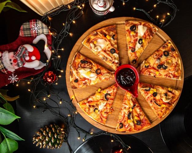 Bovenaanzicht van gesneden kip pizza geserveerd met saus