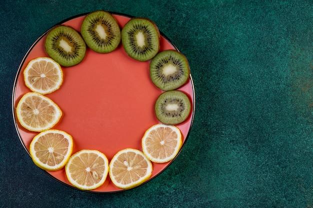 Bovenaanzicht van gesneden kiwi en citroen op plaat op donkergroen met kopie ruimte