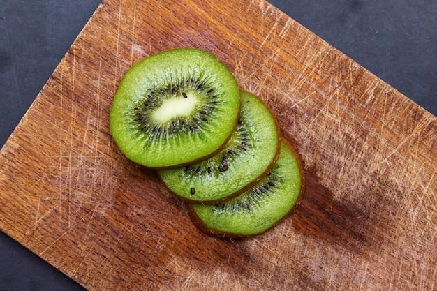Bovenaanzicht van gesneden kiwi's op een houten bord op tafel