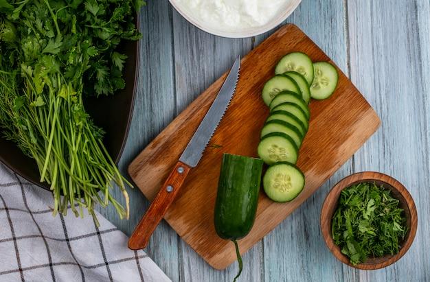 Bovenaanzicht van gesneden komkommers op een bord met een mes en groenen op een grijze ondergrond
