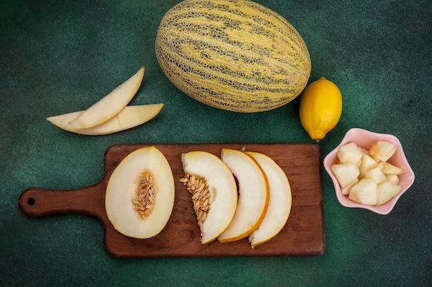 Bovenaanzicht van gesneden meloen op een houten keuken bord met plakjes meloen op een roze kom met citroen op groene ondergrond