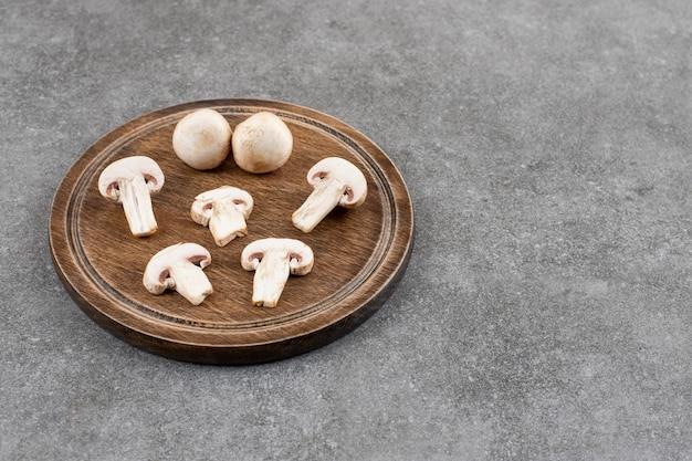 Bovenaanzicht van gesneden of hele champignons op een houten bord over grijze tafel.