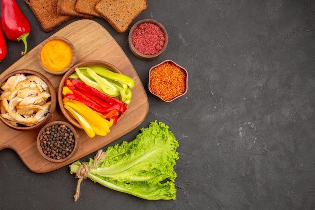 Bovenaanzicht van gesneden paprika met kruiden en brood op zwart