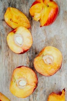 Bovenaanzicht van gesneden perziken op houten oppervlak