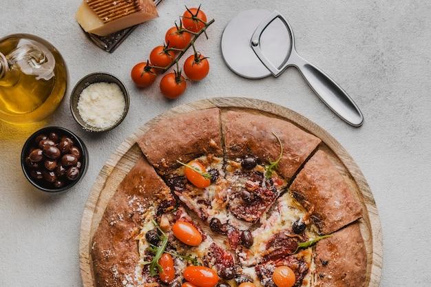 Bovenaanzicht van gesneden pizza met parmezaanse kaas en cutter