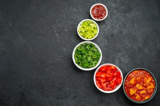 Bovenaanzicht van gesneden rode tomaten met groen op grijs