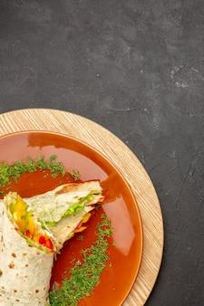 Bovenaanzicht van gesneden shaurma heerlijke vleessandwich in bruine plaat op zwart